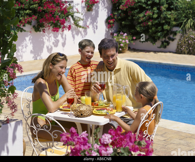 Young family enjoying lunch on villa terrace by the for Kids on the terrace