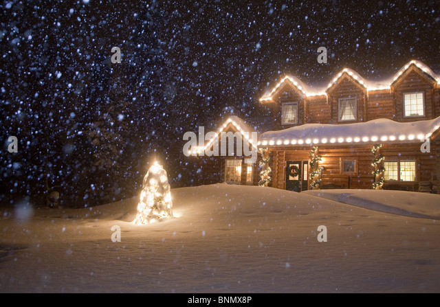 log home decorated with christmas lights with snow falling overhead