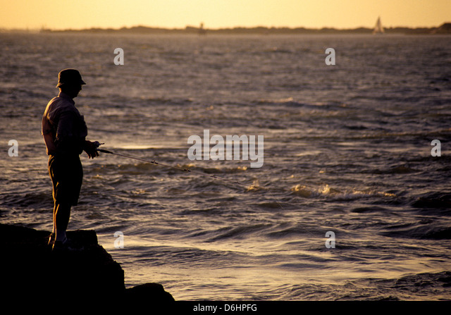 Man fishing on the jetties at port aransas texas stock for Port aransas jetty fishing report