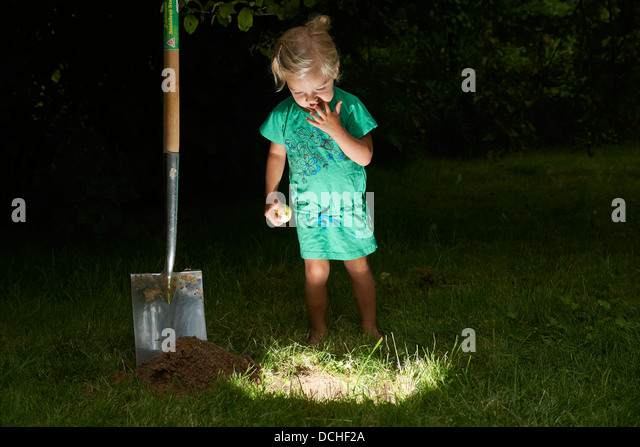 Child blond baby girl stands and digging for lighting hole for Digging ground dream meaning